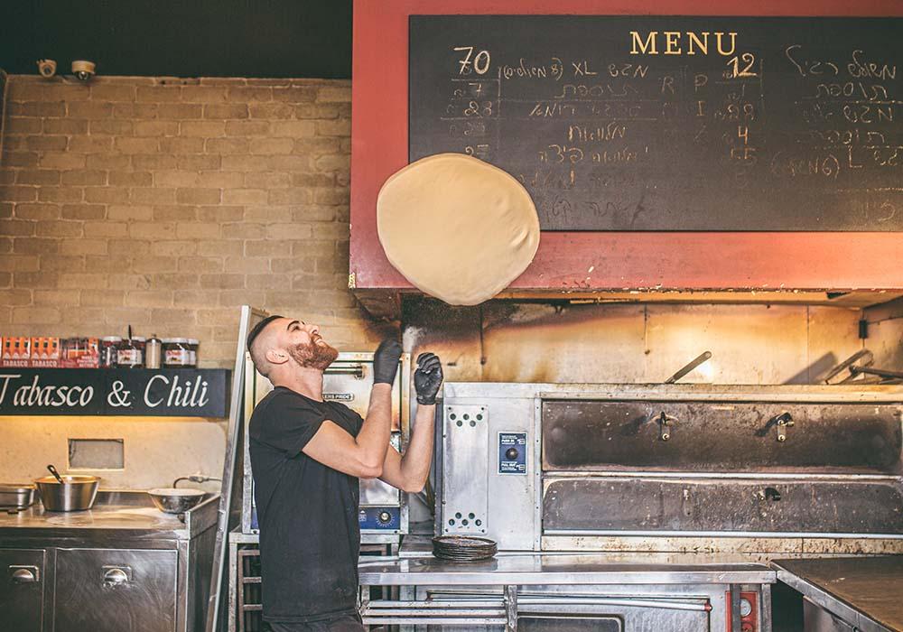 בחור מניף בצק לפיצה